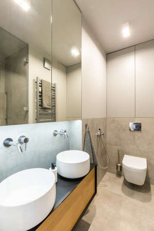 Mirror above white washbasins in beige bathroom interior with light and toilet. Real photo 스톡 콘텐츠