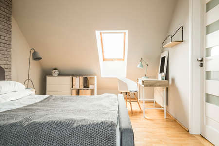 Real photo of bright Nordic style attic room interior with wooden desk with lamp, white cupboard and bed with knit blanket
