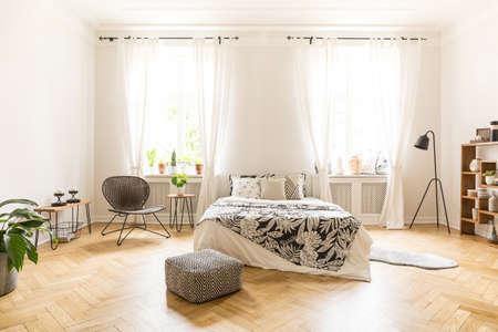 Vorderansicht eines einfachen Schlafzimmerinnenraums mit einem Bett, einem Hocker, Fenstern und Holzboden