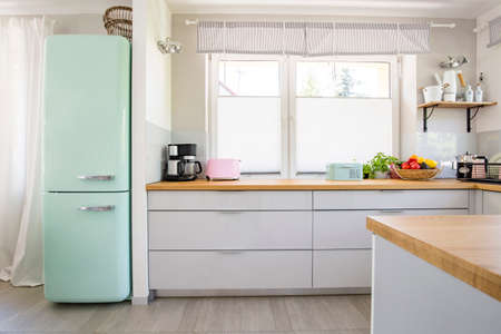 Neo mint fridge standing in real photo of bright kitchen interior with window, fresh fruits and pastel appliances placed on countertop