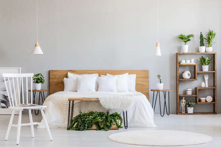 White chair near bed with wooden headboard in bright bedroom interior with plants. Real photo