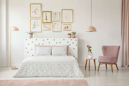 Pastel lamp above table with flower and pink armchair in womans bedroom interior with bed