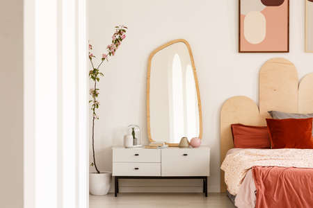 Plant next to white dressing table with mirror in red bedroom interior with poster above bed. Real photo