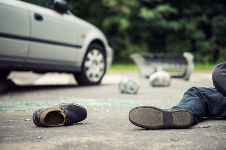 Close-up of a shoe lying next to a car crash victim with a blurred car in the background Фото со стока