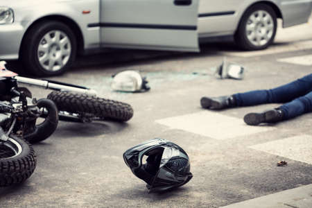 Helmet, motorbike and driver lying on a street after a car accident