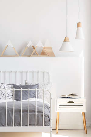 Lamps above bedside cabinet next to bed in white child's bedroom interior with triangles. Real photo