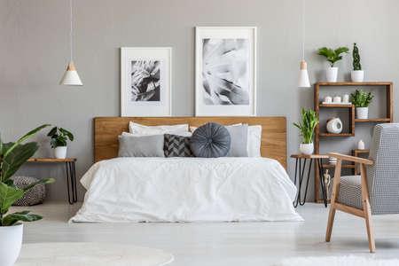 Des affiches et des lampes au-dessus de lit en bois à l'intérieur de la chambre grise avec fauteuil à motifs. Vrai photo Banque d'images