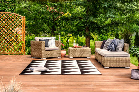 Geometrical rug and rattan furniture on a terrace in a garden full of trees Stock Photo