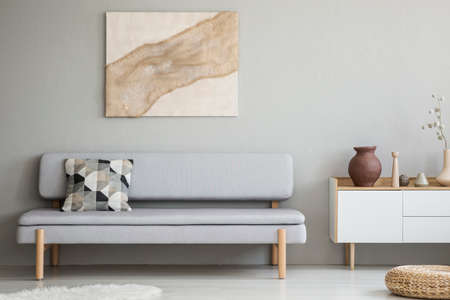 Painting on grey wall above settee with cushion in modern living room interior with cupboard. Real photo Reklamní fotografie