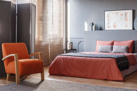 Orange armchair next to pink bed in modern grey bedroom interior with screen and poster