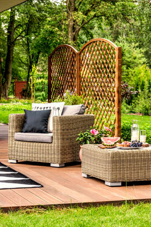 Rattan armchair with pillows and table on a terrace in a beautiful green yard