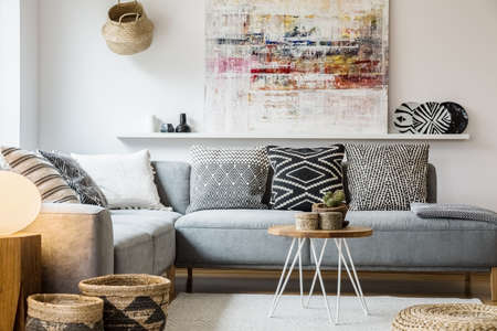 Real photo of a cozy couch with cushions standing behind a small table and in front of a shelf with a painting in boho living room interior with baskets and white rug