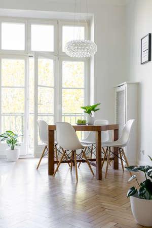 Sillas blancas en la mesa debajo de la lámpara en el luminoso comedor interior con balcón. Foto real Foto de archivo