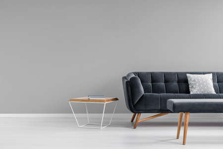 Diamond shape side table, a trendy, dark sofa and an upholstered bench in a gray living room interior with copy space. Real photo. Reklamní fotografie