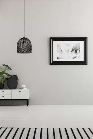 Classy, monochromatic living room interior with a creative ceiling lamp shade and place for an armchair. Real photo.