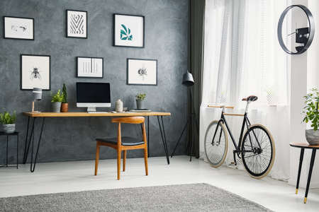 Bicycle next to wooden chair at desk in grey home office interior with posters. Real photo Stock Photo