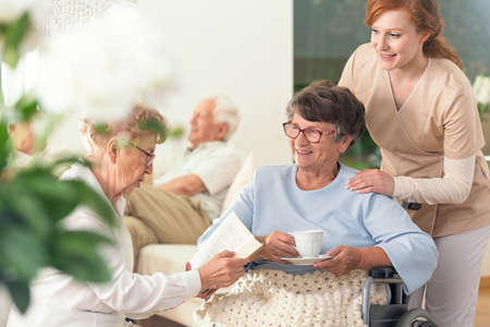 Two senior pensioners enjoying their leisure time together inside a private nursing home. Tender caretaker in uniform standing next to them Stock Photo