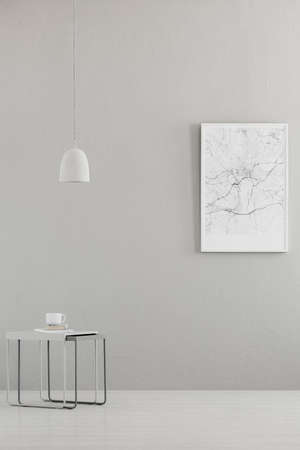 Pendant light above a modern table and a city map poster on a gray wall in a minimalist living room interior and place for a sofa. Real photo.
