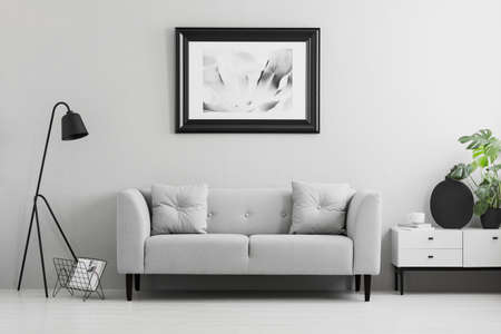 Ingelijste foto op een muur boven een chique, grijze bank met kussens in een minimalistisch woonkamerinterieur en plaats voor een tafel. Echte foto. Stockfoto