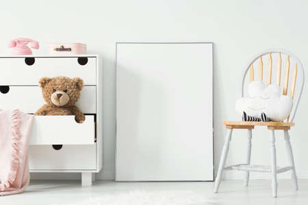 Mockup of empty poster and cabinet with plush toy and pink blanket in white child's room interior. Real photo with a place for your graphic