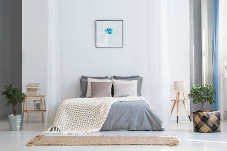 Simple poster above bed with knit blanket in bright bedroom interior with plants and rug. Real photo