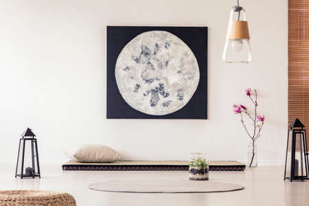 Moon poster above mat with pillow in japanese bedroom interior with lanterns and flowers. Real photo Stock Photo