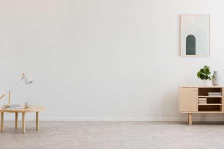 Lampka biurkowa na stoliku i prostej, drewnianej szafce w pustym wnętrzu salonu z białą ścianą i miejscem na sofę. Prawdziwe zdjęcie.