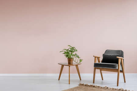 Wooden armchair with gray upholstery and a side table in a pastel pink living room interior with place for a bookcase. Real photo.