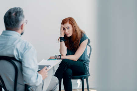 Scared young woman talking to a therapist about abuse in a bright office Stock Photo
