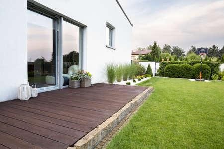 Leere hölzerne Terrasse des weißen Hauses mit grünem Gras und Bäumen. Echtes Foto
