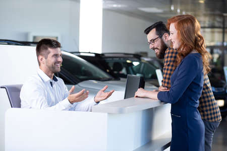 Smiling car seller talking with happy buyers in exclusive showroom Stockfoto