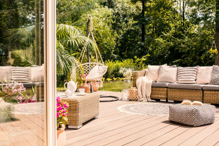 Pouf and rattan sofa on wooden patio with hanging chair in the garden. Real photo Stock Photo