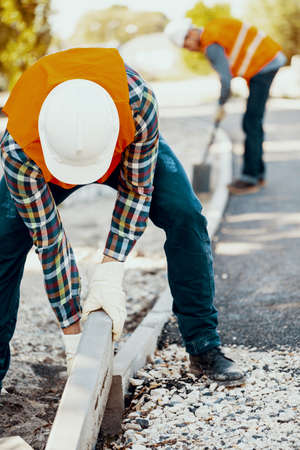Builder in a hardhat and vest making a curb on the roadworks Stockfoto