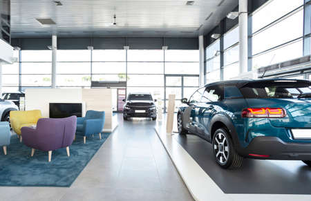 Expensive vehicles for sale and rent in car showroom with armchairs Stockfoto