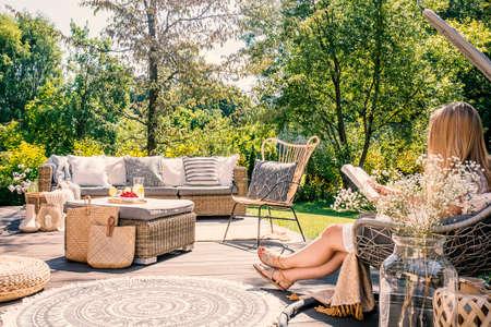 Frau, die Buch liest, während an der Terrasse mit Rattanmöbeln im Garten entspannend. Echtes Foto Standard-Bild