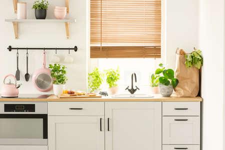 Foto reale di armadi da cucina, piano di lavoro con piante, cibo e borsa della spesa e finestra con persiane all'interno di una cucina
