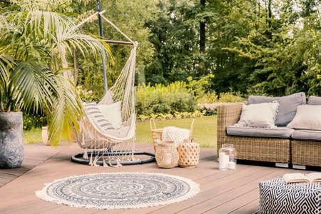 Almohadas en hamaca en terraza con alfombra redonda y sofá de ratán en el jardín. Foto real