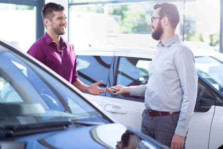 Professional car dealer giving keys to buyer in dealing salon