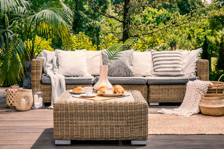 Rattan table and pillows on couch standing on a patio in the garden during summer. Real photo