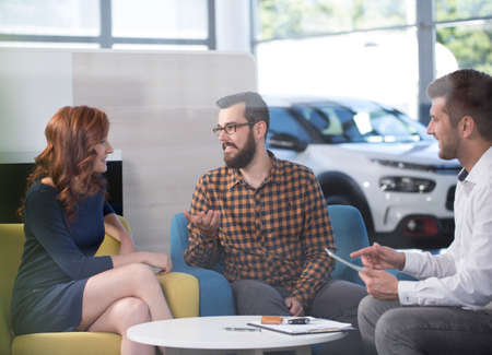 Marriage talking about new car in the dealing salon with professional seller