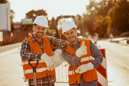 Zwei Bauarbeiter in Schutzhelmen und Westen posieren für ein Foto an der Straße Standard-Bild