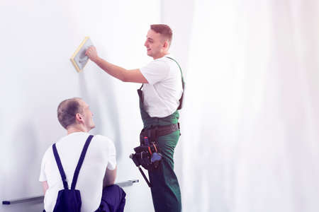 Workers in uniforms talking during renovating a home. Place your graphic on an empty wall Stock fotó
