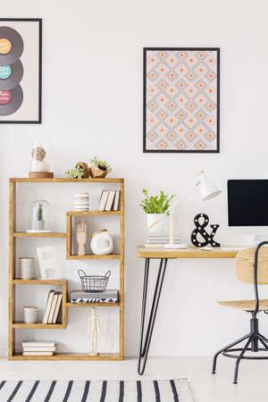 Poster above wooden desk with plant and desktop computer in home office interior. Real photo