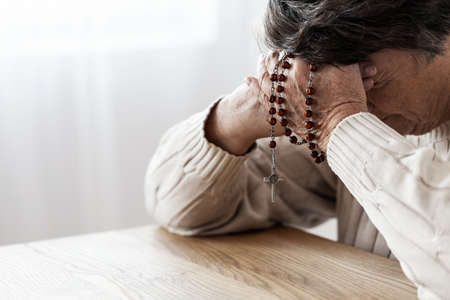 Elderly person in melancholy praying with rosary in church Stock Photo
