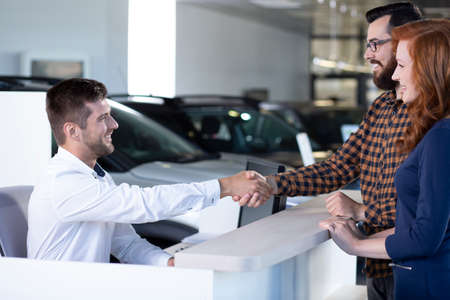 Car dealer and buyer shaking hands after transaction in luxury dealing salon 写真素材