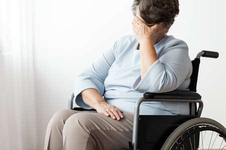 Sad disabled senior woman in a wheelchair in a nursing house