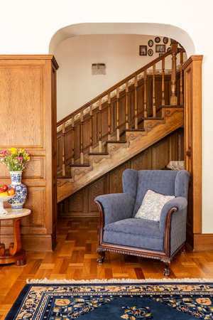 Blue armchair against wooden stairs in classic living room interior with flowers and carpet. Real photo Imagens