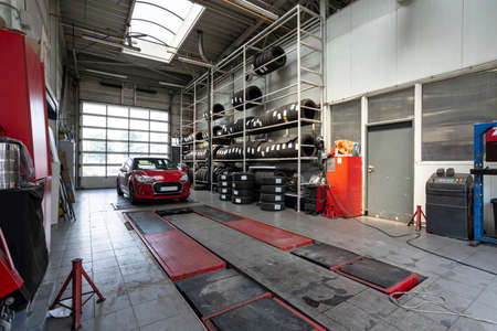 Red car in a workshop with tires. Professional vehicle repair Stockfoto