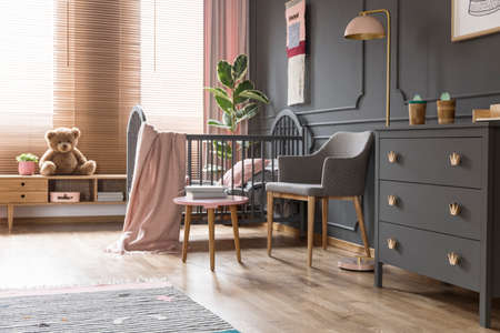 Real photo of a cot standing next to an armchair, lamp and cupboard in dark and classic baby room interior Editorial