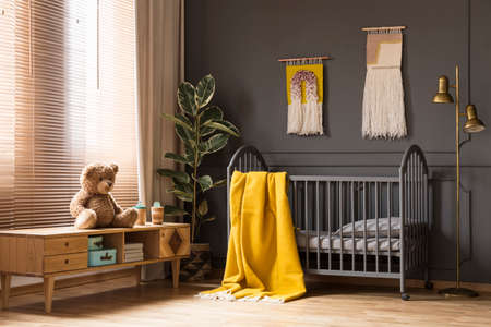 Real photo of a cot with a yellow blanket standing between a low cupboard with a teddy bear and a lamp in baby room interior Imagens
